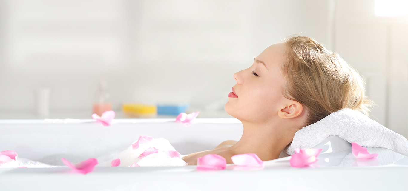 Woman laying in bathtub with flowers and soap